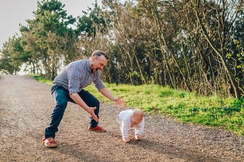 Un père apprend à marcher à son enfant. L'égalité femmes-hommes illustrée dans l'éducation des petits et petites.